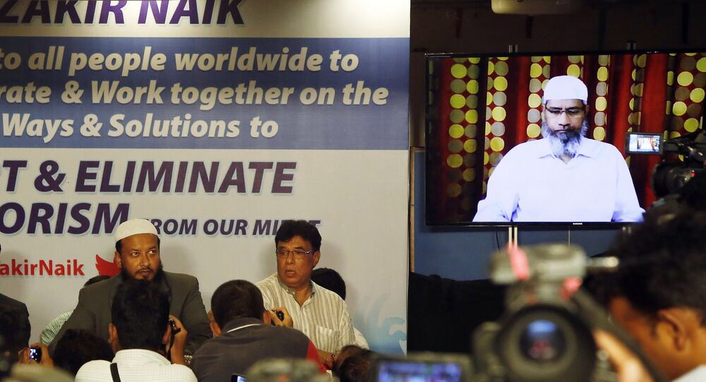 Indian journalists listen to a video conference of controversial Islamic preacher and the founder of Islamic Research Foundation, Zakir Naik, right, in Mumbai, India, Friday, July 15, 2016
