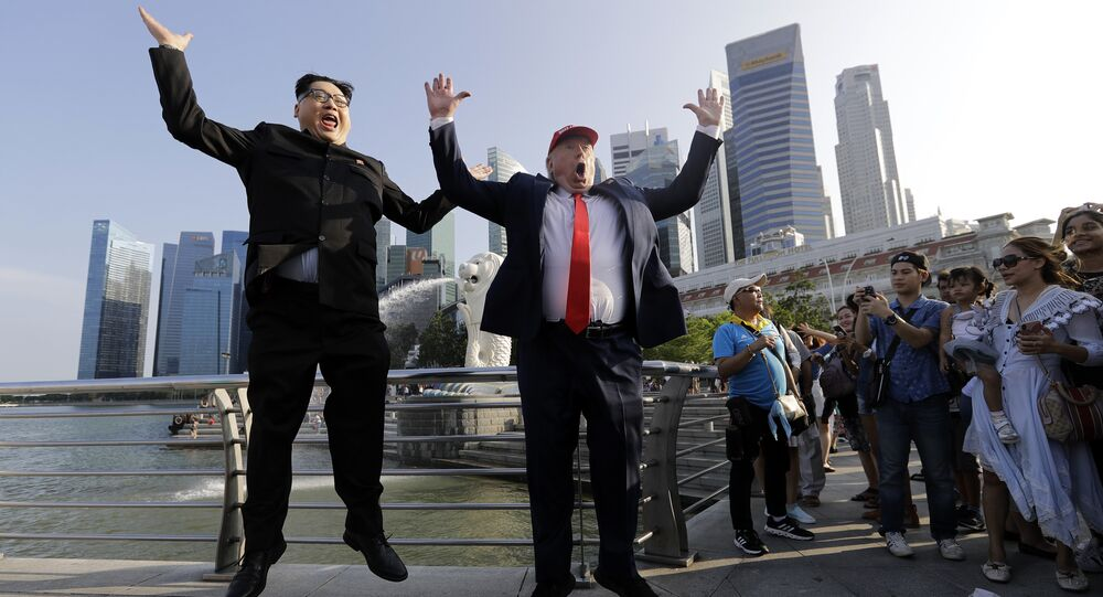 Kim Jong Un and Donald Trump impersonators, Howard X, left, and Dennis Alan, second left, pose for photographs during their visit to the Merlion Park, a popular tourist destination in Singapore, on Friday, June 8, 2018