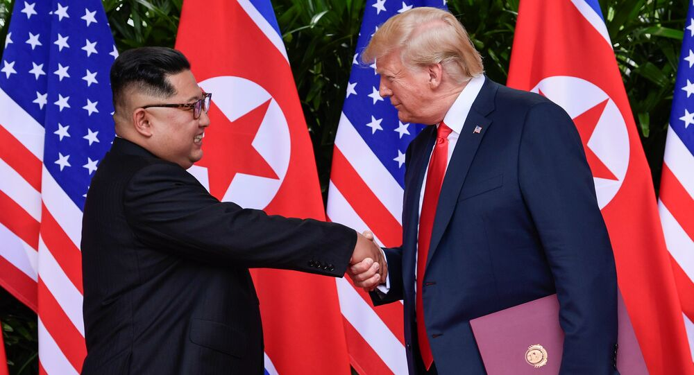 U.S. President Donald Trump and North Korea's leader Kim Jong Un shake hands during the signing of a document after their summit at the Capella Hotel on Sentosa island in Singapore June 12, 2018