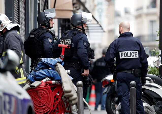 French police and a fireman secure the street as a man has taken people hostage at a business in Paris, France, June 12, 2018