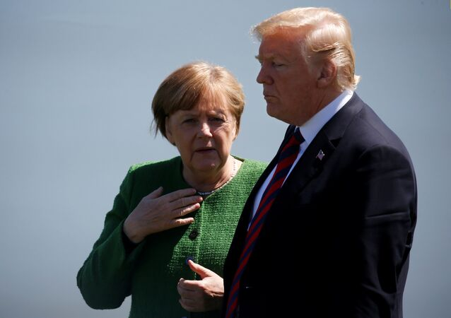 Germany's Chancellor Angela Merkel talks with U.S. President Donald Trump during a family photo at the G7 Summit in Charlevoix, Quebec, Canada, June 8, 2018