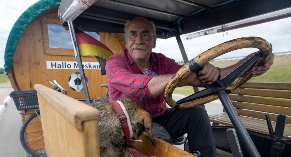 Soccer fan from Pforzheim, Germany, Hubert Wirth, 70, with his dog Hexe, drives his tractor with a trailer to attend the FIFA 2018 World Cup in Russia near the village of Yasen, Belarus June 7, 2018