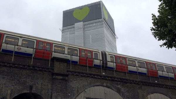 A London Underground train comes to a halt next to Grenfell Tower as a minute's silence is marked on June 14, 2018 - Sputnik International