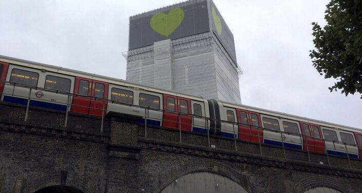 A London Underground train comes to a halt next to Grenfell Tower as a minute's silence is marked on June 14, 2018