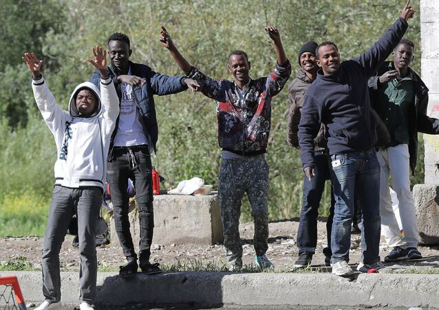 Migrants dance and cheer as they assist at the start of the citizens and solidarity march, in Ventimiglia, an Italian city near the border between Italy and France, on April 30, 2018. Some 60 people, gathered on April 30, 2018 in Ventimiglia at the French and Italian border