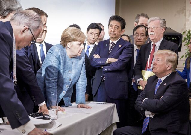 German Chancellor Angela Merkel, center, speaks with US President Donald Trump, seated at right, during the G7 Leaders Summit in La Malbaie, Quebec, Canada, 9 June, 2018