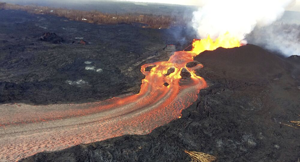 In this Sunday, June 10, 2018 photo from the U.S. Geological Survey, fissure 8 below Kilauea Volcano continues to erupt vigorously with lava streaming through a channel that reaches the ocean at Kapoho Bay on the island of Hawaii . The width of the active part of the lava channel varies along its length, but ranges from about 100 to 300 meters (yards) wide. A clear view of the cinder-and-spatter cone that's building around the vent from ongoing lava fountains can be seen here.