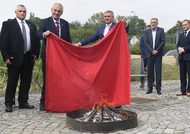 Czech President Milos Zeman (2ndL) and Chancellor of the Office of the President Vratislav Mynar (C) burn a large piece of red textile, which refers to an oversized red underwear that was one of the symbols of political opponents, during its ritual burning on June 14, 2018 at the Prague Castle in the Czech capital