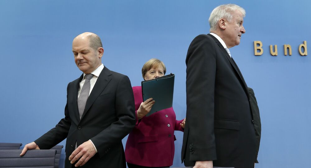 In this March 12, 2018 photo, from left, Olaf Scholz, acting chairman of the German Social Democratic Party (SPD), German Chancellor and chairwoman of the German Christian Democratic Union (CDU), Angela Merkel, and the chairman of the German Christian Social Union (CSU), Horst Seehofer, arrive for a joint press conference in Berlin, Germany