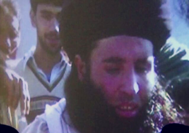 In this image made from video broadcast in 2013, undated footage of Mullah Fazlullah is shown on a projector in Pakistan. Fazlullah was the emir of the Tehrik-e-Taliban Pakistan (TTP) before he was reportedly killed in a drone strike on June 15, 2018.