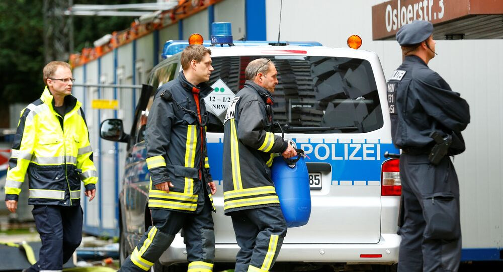 An official carries a plastic barrel outside the apartment of 29-year-old Sief Allah H., in Cologne, Germany, June 15, 2018, a Tunisian man who was detained on June 13, 2018, suspected of planning an Islamist-motivated attack and the manufacturing of a biological weapon using ricin