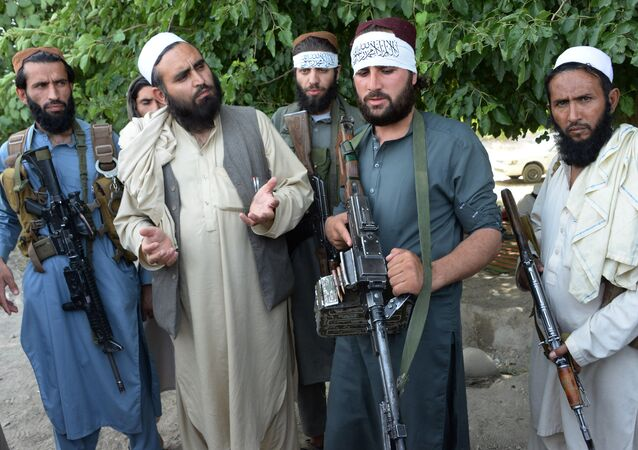 Afghan Taliban militants stand with residents as they took to the street to celebrate ceasefire on the second day of Eid in the outskirts of Jalalabad on June 16,2018