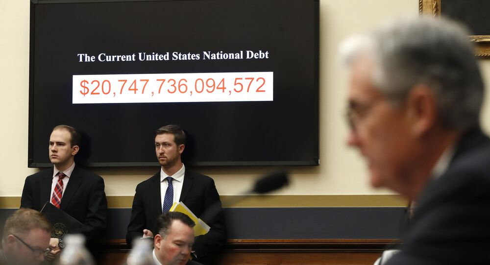 The National debt is shown behind Federal Reserve Chairman Jerome Powell as he testifies on the semiannual monetary policy report to the House Financial Services Committee, Tuesday, Feb. 27, 2018, in Washington