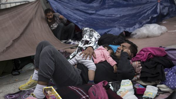 A migrant father and child rest outside the El Chaparral port of entry building at the US-Mexico border in Tijuana, Mexico - Sputnik International
