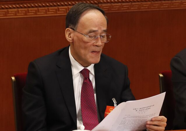 Chinese Vice President Wang Qishan reads a document during the closing session of the annual National People's Congress in the Great Hall of the People in Beijing, China, Tuesday, March 20, 2018