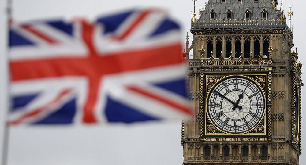 a British flag is blown by the wind near to Big Ben's clock tower in front of the UK Houses of Parliament in central London