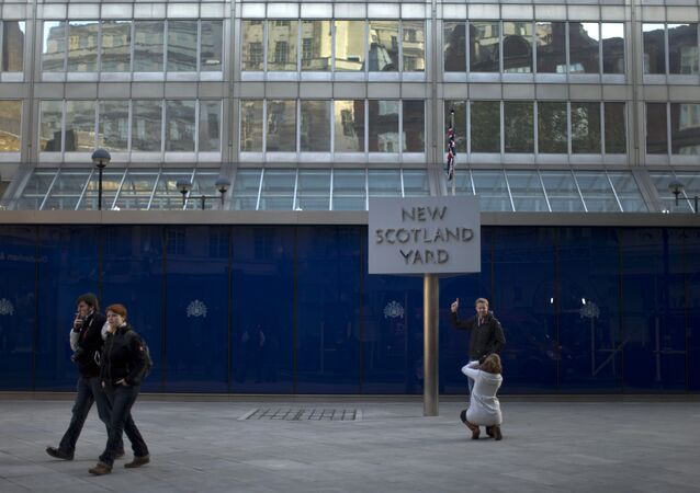 A tourist poses for a photograph by the rotating sign outside New Scotland Yard, the headquarters building of London's Metropolitan Police force in central London