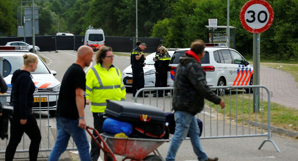 Visitiors leave the festival grounds as police are seen near a scene where a van struck into people after a concert in Landgraaf, the Netherlands June 18, 2018