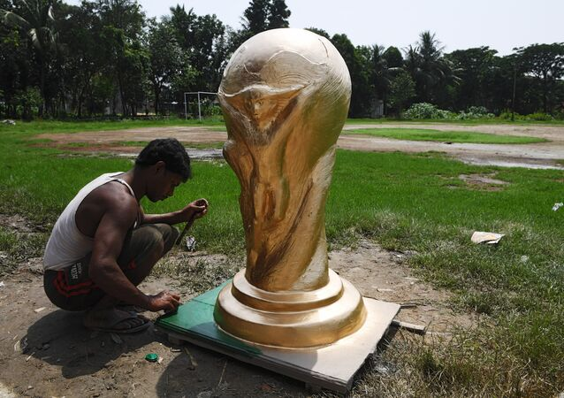 An Indian artisan works on clay model of the FIFA world cup trophy ordered by football fan clubs for decoration, ahead of the upcoming FIFA Russia 2018 World Cup, in Kolkata on June 13, 2018