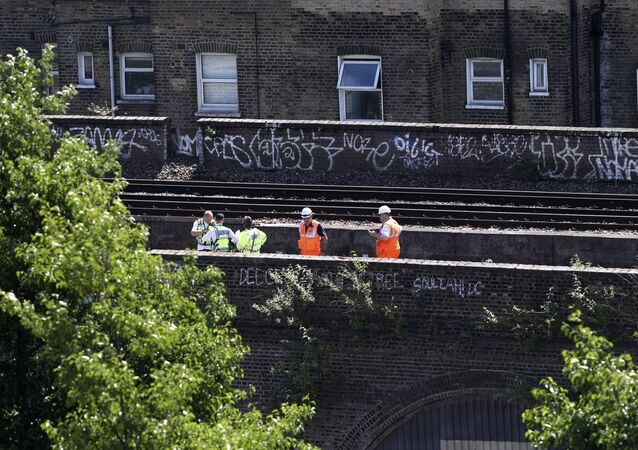 British Transport Police and railway workers inspect the scene where three graffiti artists died on Monday, June 18