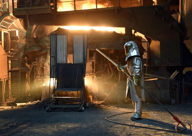 A steelworker in a protective suit checks the temperature of molten metal in furnace at the TMK Ipsco Koppel plant in Koppel, Pennsylvania on March 9, 2018