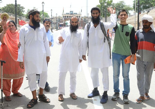Pakistani former prisoners Nasreen Akhtar (L), Mohammad Yasin Jat (2L), Mohammad Nadeem (C), Akhtar Ul Islam Teeli (3R), Haroon Ali (2R) and Altab(R) wave as they prepare to cross the India-Pakistan border in Wagah, about 35 km from Amritsar on June 19, 2018