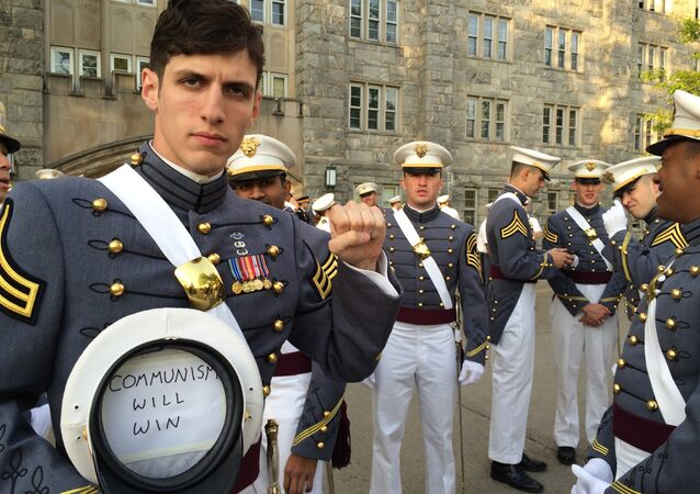 In this May 2016 photo provided by Spenser Rapone, Rapone raises his left fist while displaying a sign inside his hat that reads Communism will win, after graduating from the United States Military Academy at West Point, N.Y.