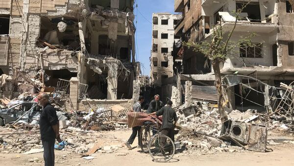 People stand in front of damaged buildings, in the town of Douma, the site of a suspected chemical weapons attack, near Damascus, Syria, Monday, April 16, 2018 - Sputnik International