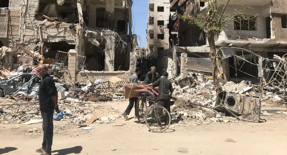 People stand in front of damaged buildings, in the town of Douma, the site of a suspected chemical weapons attack, near Damascus, Syria, Monday, April 16, 2018