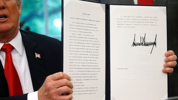U.S. President Donald Trump displays an executive order on immigration policy after signing it in the Oval Office at the White House in Washington, U.S., June 20, 2018. - Sputnik International