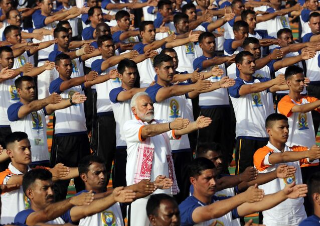 Indian Prime Minister Narendra Modi, center, performs yoga along with thousands of Indians to mark International Day of Yoga in Dehradun, India, Thursday, June 21, 2018