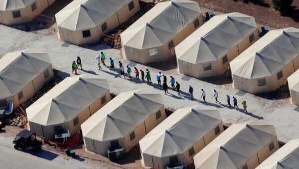 Immigrant children now housed in a tent encampment under the new zero tolerance policy by the Trump administration are shown walking in single file at the facility near the Mexican border in Tornillo, Texas, U.S. June 19, 2018 - Sputnik International