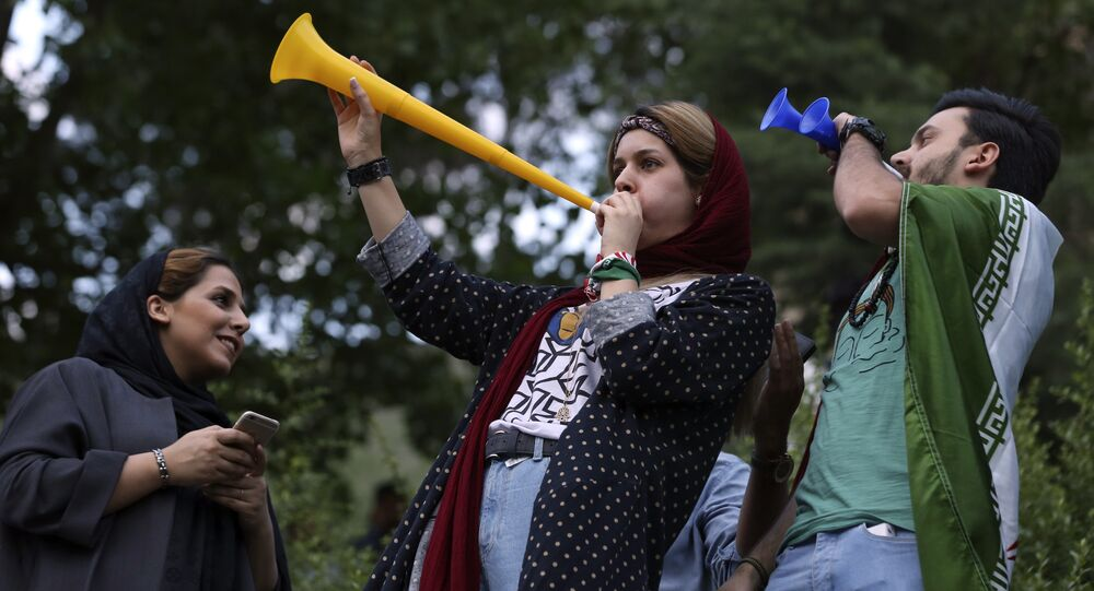Iranian fans blow horns while watching the national soccer team play against Morocco in the 2018 World Cup, on a giant screen in a park in Tehran, Iran, Friday, June 15, 2018