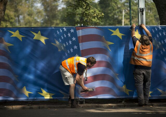 Workers hang drapes with U.S. and European flag designs on a fence in preparation for the start of the Ryder Cup golf tournament in Gleneagles, Scotland, Sunday, Sept. 21, 2014
