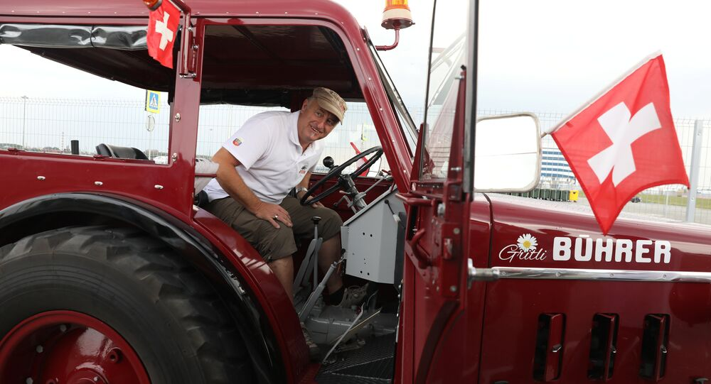 Swiss fan Beat Studer looks at an old-time tractor after driving with two friends, from home to Kaliningrad stadium to watch their team playing against Serbia, in Kaliningrad, Russia June 21, 2018.