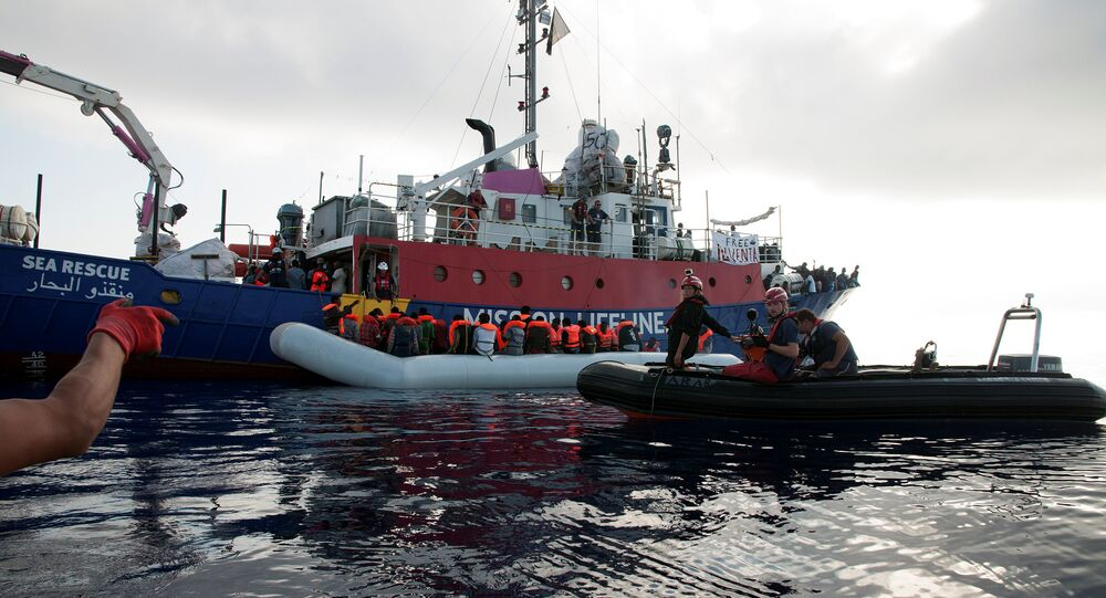 Migrants are seen in a rubber dinghy as they are rescued by the crew of the Mission Lifeline rescue boat in the central Mediterranean Sea, June 21, 2018