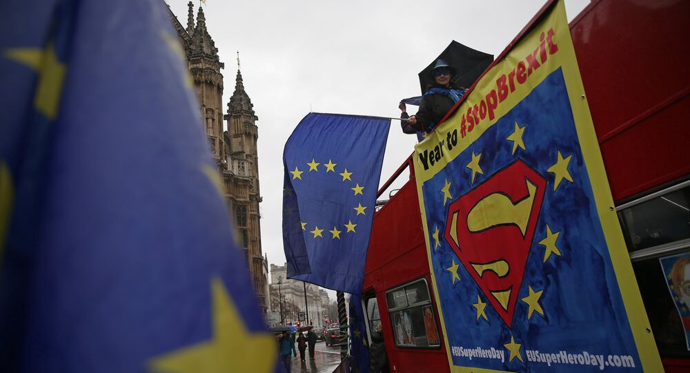 (File) Anti-Brexit demonstrators wave European Union flags from the top deck of a bus parked outside the Houses of Parliament in London on March 29, 2018