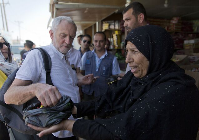 The UK's Labour party leader Jeremy Corbyn is offered candy by Syrian refugee Sohela Sobeihi, 52 while talking to refugees at the main market road, during his visit to the Zaatari Syrian Refugee Camp, in Mafraq, Jordan, June 22, 2018