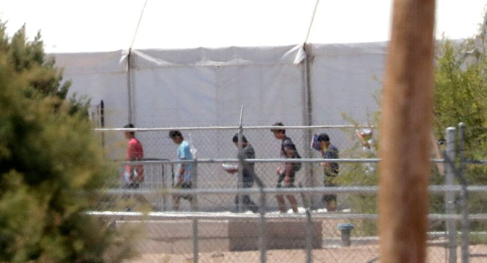Detainees are seen outside tent shelters used to hold separated family members, Friday, June 22, in Fabens, Texas. The U.N human rights office says President Donald Trump's decision to stop the U.S. policy separating migrant parents from their children doesn't go far enough