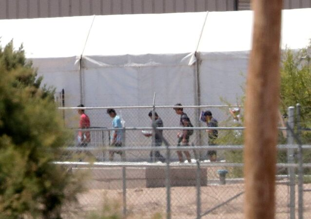 Detainees are seen outside tent shelters used to hold separated family members, 22 June, in Fabens, Texas. The UN human rights office says President Donald Trump's decision to stop the US policy separating migrant parents from their children doesn't go far enough