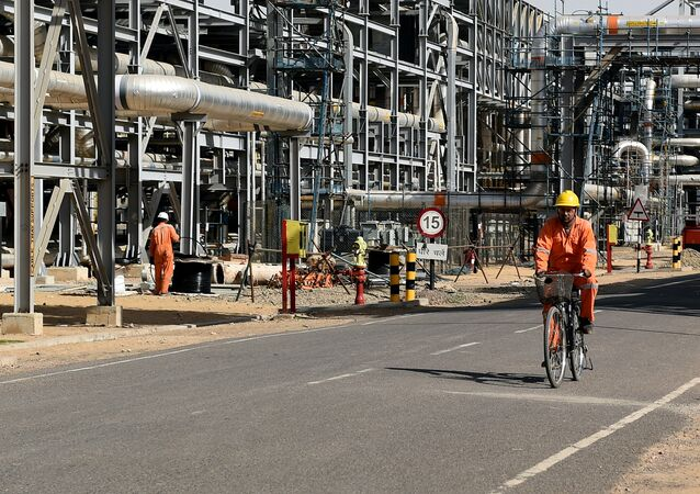 In this photograph taken on December 11, 2015, a worker cycles by machinery at Cairn India, Oil and Gas exploration plant at Barmer in Rajasthan