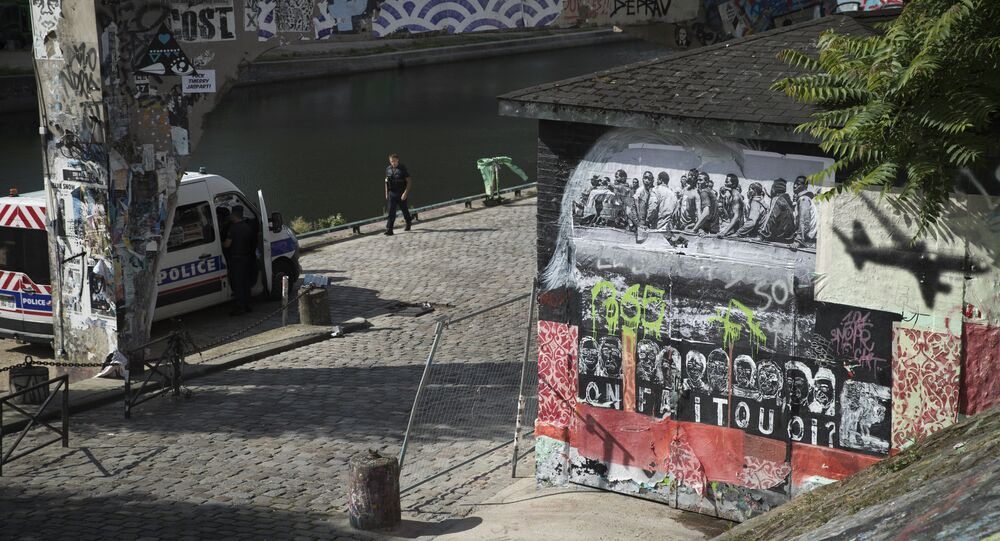 French police officer patrol past a mural depicting migrants (L) and an aeroplane (R) with the words underneath that read, 'What do we do?' painted and plastered on a structure along the banks of Canal Saint Martin where a former migrants camp was evacuated by the French authorities, on June 13, 2018