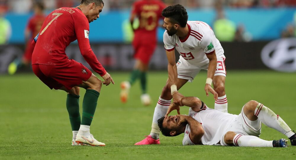 Portugal's Cristiano Ronaldo reacts as Iran's Morteza Pouraliganji is on the floor. File photo