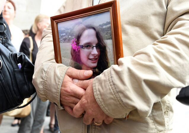 FILES) In this file photo taken on June 6, 2018 a man holds a picture of murdered French au-pair Sophie Lionnet after her funeral in Sens