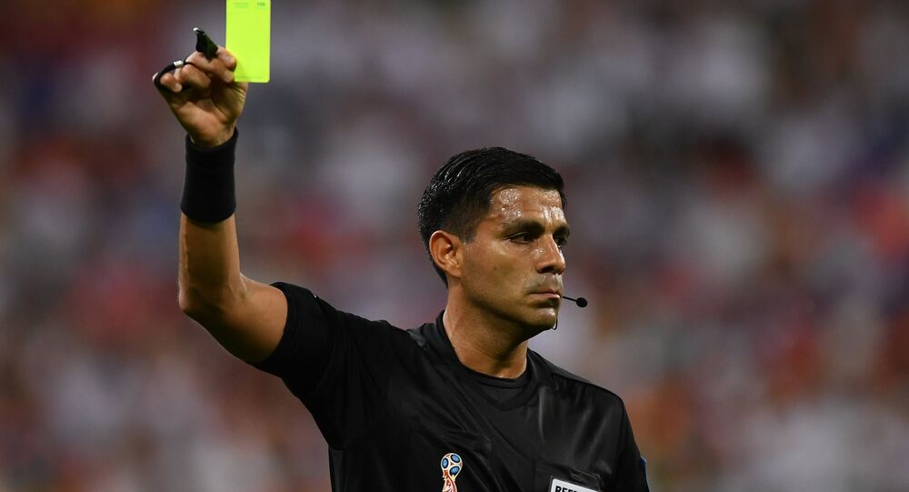 Referee Enrique Caceres shows a yellow card during the World Cup Group B soccer match between Iran and Portugal at the Mordovia Arena, in Saransk, Russia, June 25, 2018.