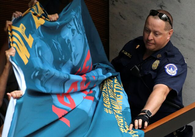 A U.S. Capitol Police officer attempts to take a protest banner from demonstrators calling for an end to family detention and in opposition to the immigration policies of the Trump administration, at the Hart Senate Office Building on Capitol Hill in Washington, U.S. June 28, 2018