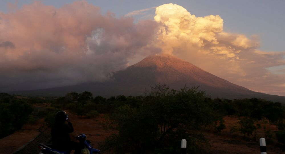 A motorist takes pictures of Mount Agung volcano erupting in Kubu, Karangasem Regency in Bali, Indonesia on June 29, 2018