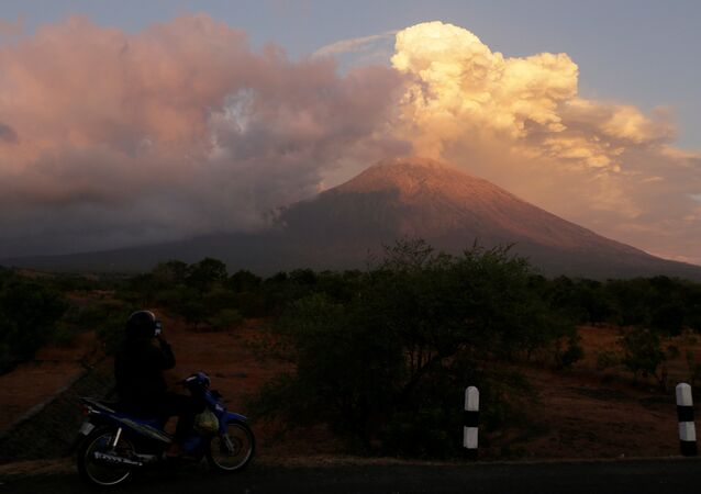 A motorist takes pictures of Mount Agung volcano erupting in Kubu, Karangasem Regency in Bali, Indonesia on June 29, 2018