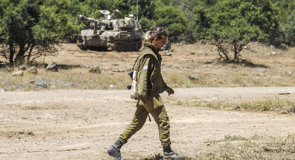 An Israeli soldier walks as a mobile artillery piece is seen deployed in the background near the border with Syria in the Israeli-annexed Syrian Golan Heights on July 1, 2018