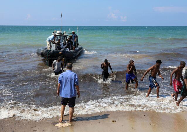 Migrants leave a boat at the coast of Tajoura, east of Tripoli, Libya June 20, 2018